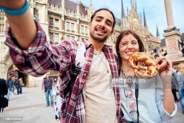 young couple taking a selfie with brezel in munich, germany - marienplatz stock pictures, royalty-free photos & images
