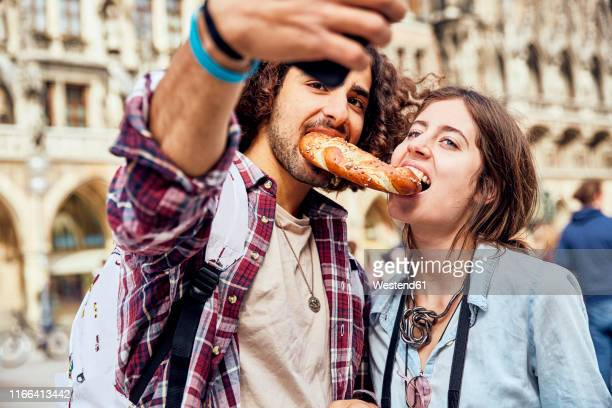 young couple taking a selfie with brezel in the mouth, munich, germany - munich stock pictures, royalty-free photos & images