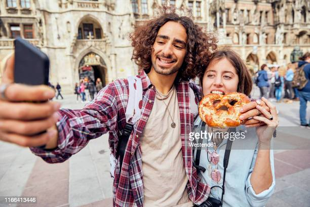 young couple taking a selfie with brezel in the mouth, munich, germany - new town hall munich stock pictures, royalty-free photos & images