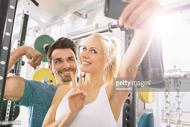 Young couple taking a selfie with smartphone after training at gym