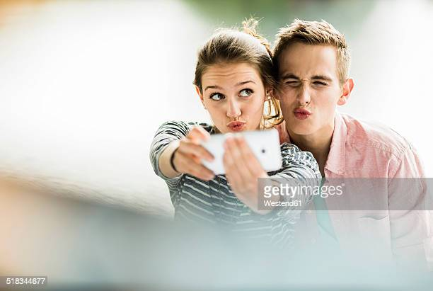 young couple taking a selfie with smartphone - verlieben stock-fotos und bilder