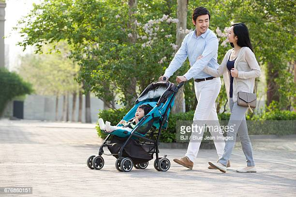 young couple taking a walk with their baby in pram - 乳母車 ストックフォトと画像