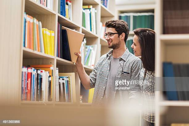 Young couple taking books in a library.