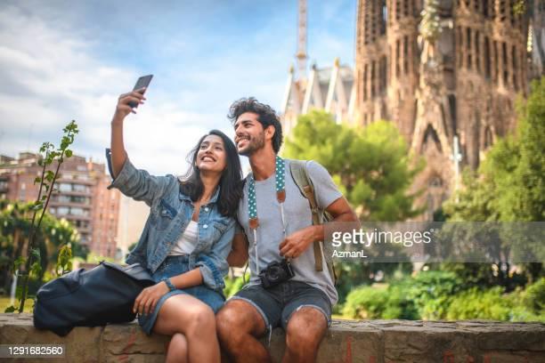 young couple taking break from sightseeing for selfie - international landmark imagens e fotografias de stock