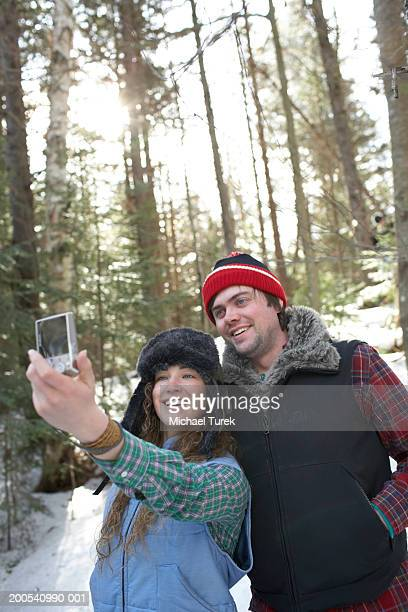 young couple taking digital self portrait in woods, winter - lake placid stock pictures, royalty-free photos & images