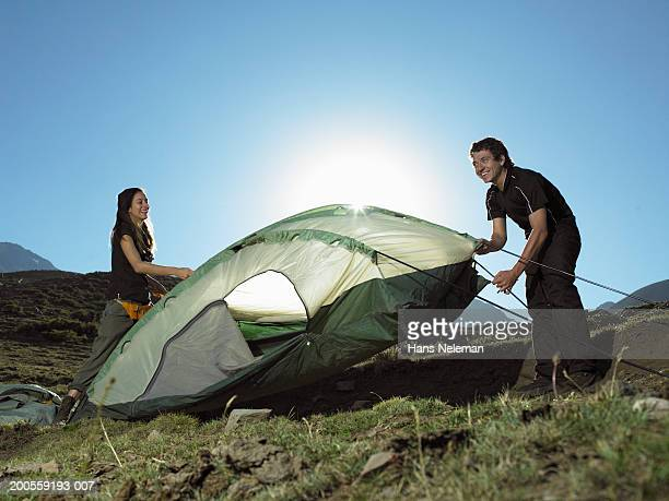 Young couple taking down tent, smiling
