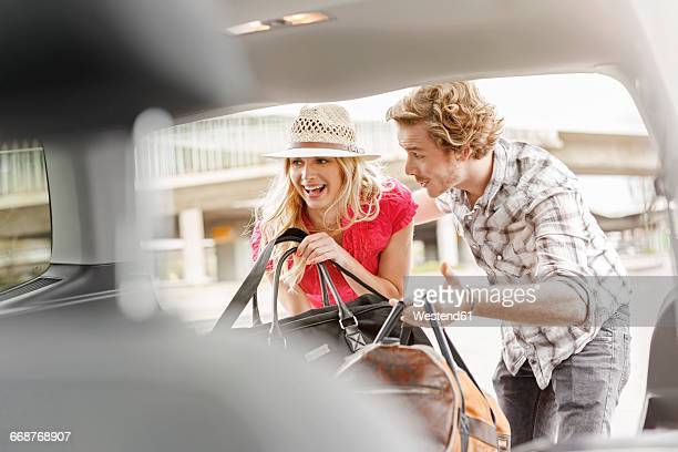 Young couple taking luggage out of car boot