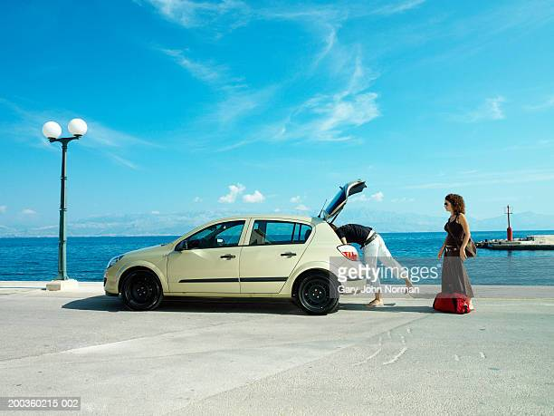 Young couple taking luggage out of car near ocean, side view