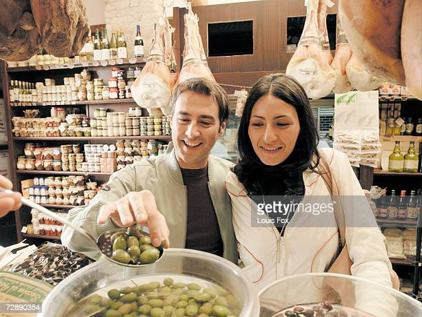 Young couple taking olives from spoon at delicatessen, counter
