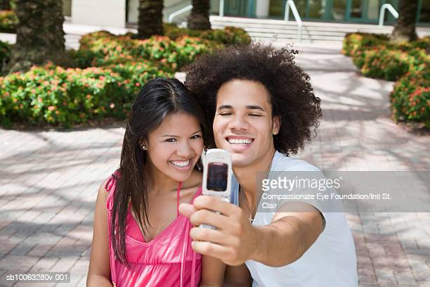 Young couple taking photo of selves with mobile phone outdoors