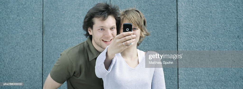 Young couple taking photo with camera phone : Stockfoto