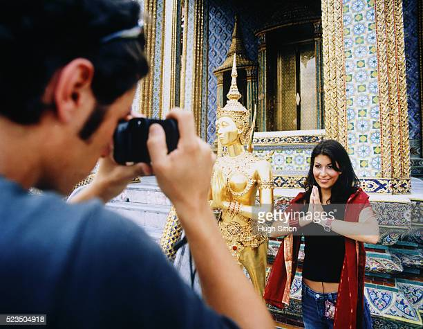 young couple taking photograph at palace - hugh sitton stockfoto's en -beelden