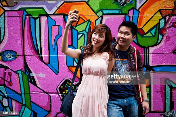 Young couple taking photograph in front of street art graffiti in Hosier Lane.
