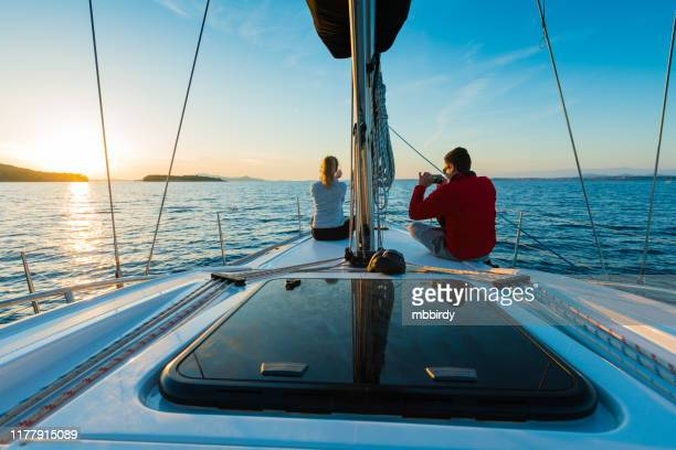 young couple taking photos at sailboat bow at sunset - sailor stock pictures, royalty-free photos & images