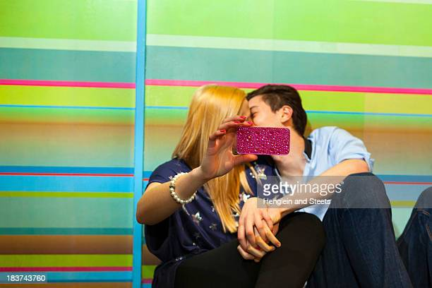 Young couple taking self portrait photograph of kiss