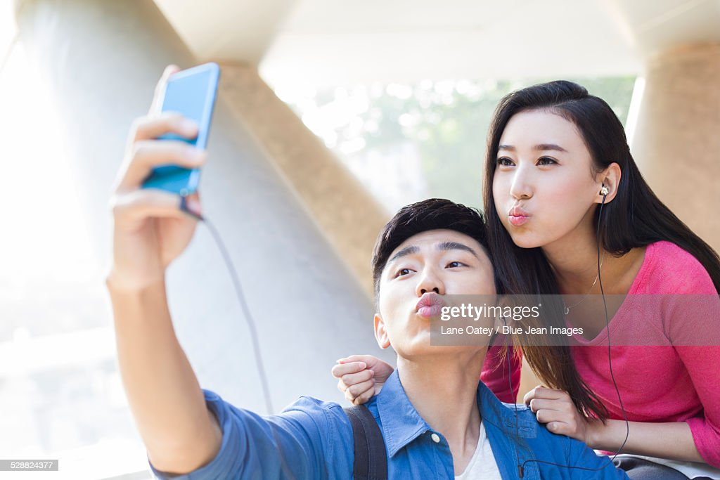 Young couple taking self portrait with a smart phone : Stock Photo