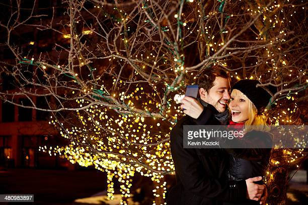 Young couple taking self portrait with city xmas lights