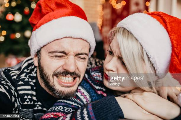 Young couple taking selfie and goofing arounf in front of a Christmas tree. He messed up things, where is my gift