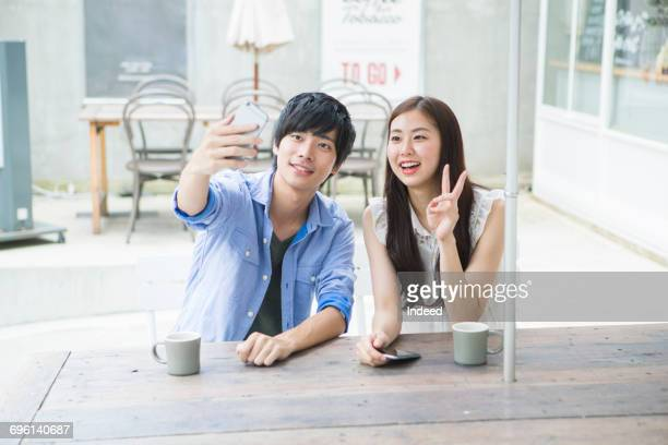 Young couple taking selfie at table