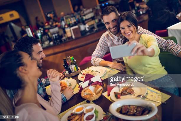 レストランで昼食中に Selfie を取って若いカップル