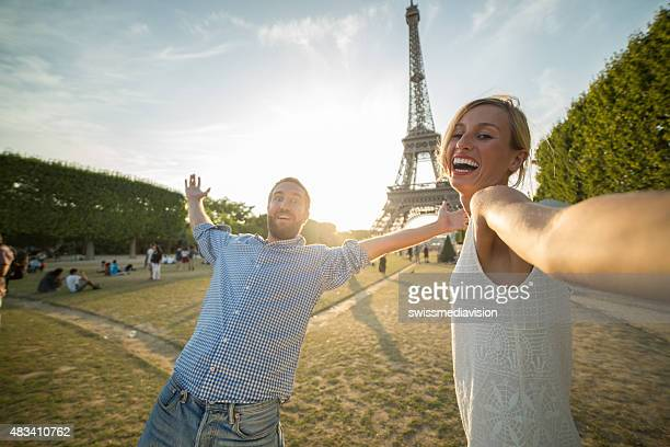 Young couple taking selfie in front of Eiffel tower-Paris