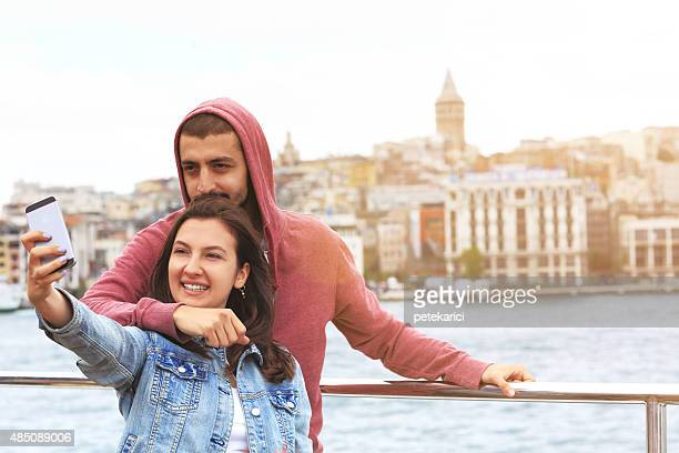 Young couple taking selfie in front of Galata tower; Istanbul