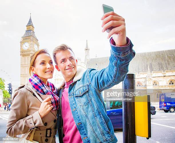 young couple taking selfie in front of london's big ben - west end london stock pictures, royalty-free photos & images