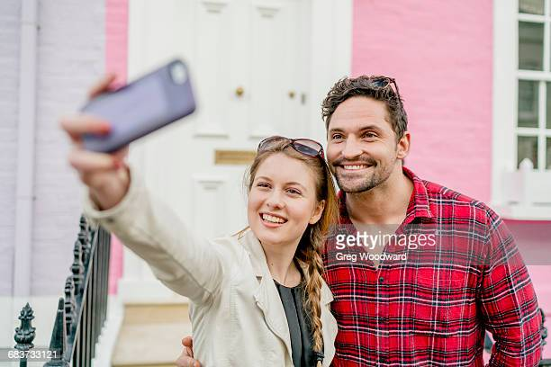 Young couple taking selfie in front of pink house, Kings Road, London, UK