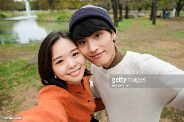 young couple taking selfie in park - self portrait photography stock pictures, royalty-free photos & images