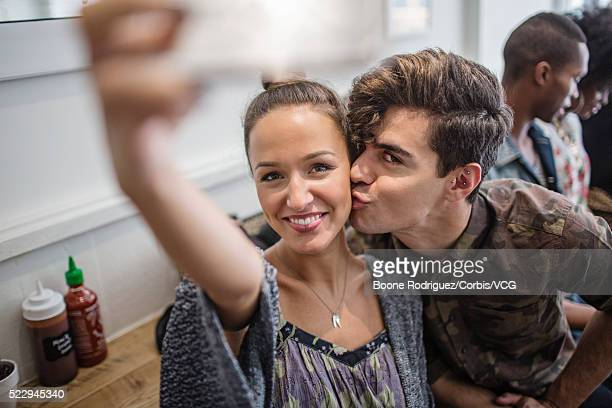 Young couple taking selfie in restaurant