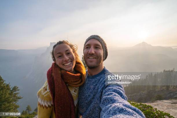 young couple taking selfie on top of yosemite valley with half dome, usa - central california stock pictures, royalty-free photos & images