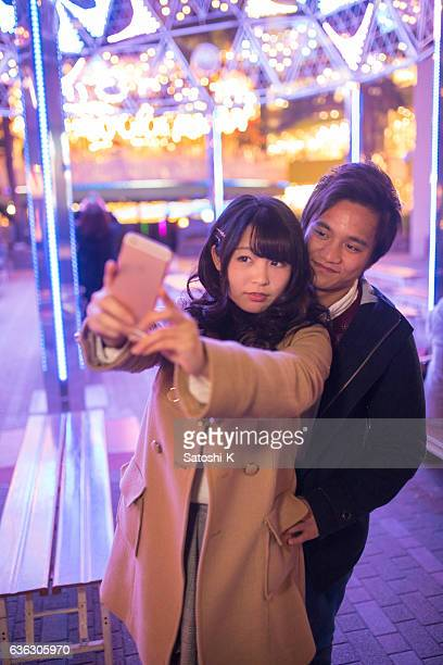 Young couple taking selfie picture under Christmas light