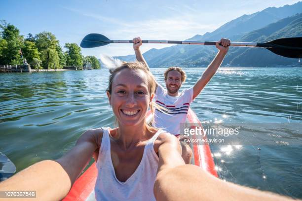 young couple taking selfie portrait in red canoe on mountain lake - weekend activities stock pictures, royalty-free photos & images