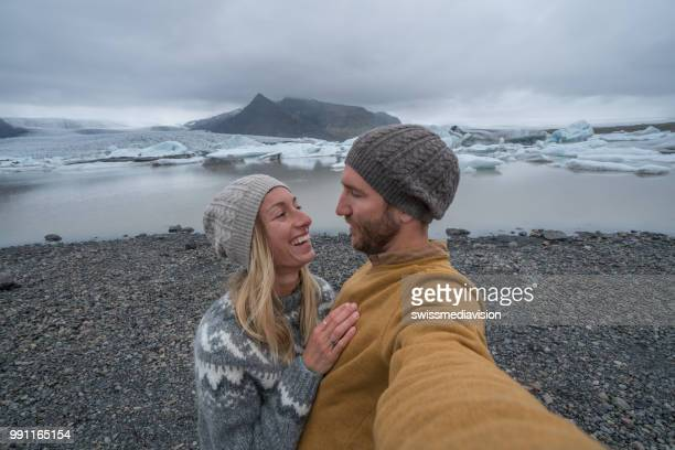 Young couple taking selfie with glacier lagoon, icebergs floating on water