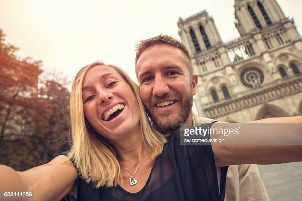 Young couple taking selfie with Notre Dame de Paris, France