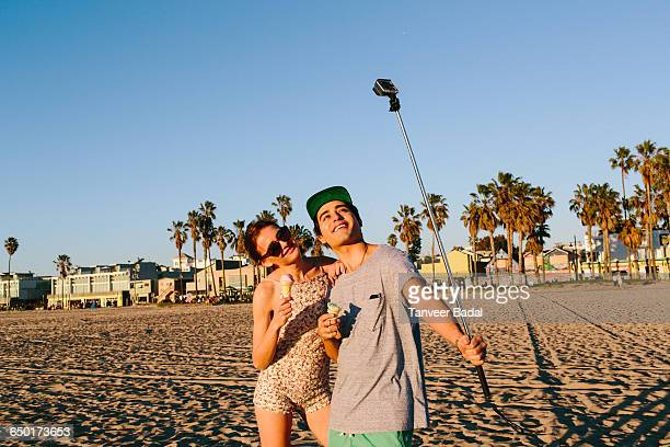 Young couple taking selfie with smartphone stick on beach, Venice Beach, California, USA
