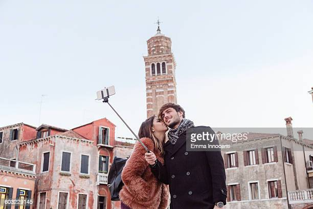 young couple taking selfie with stick on holiday