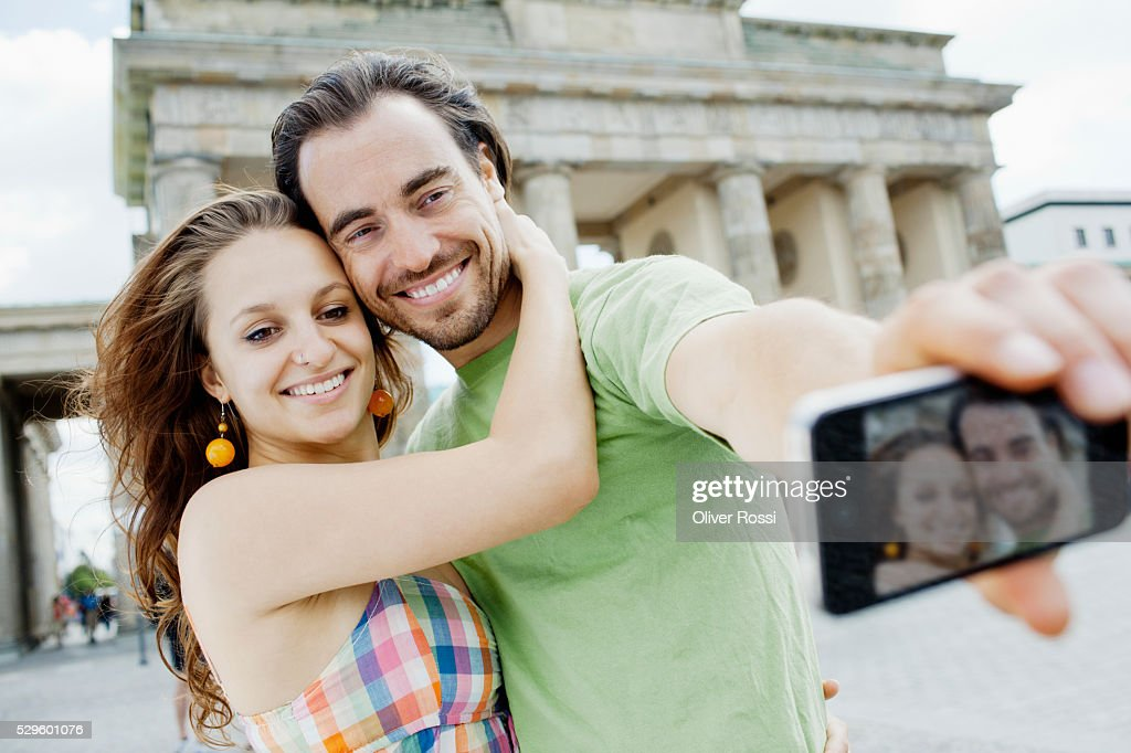 Young couple taking self-portrait photo in city : Foto de stock