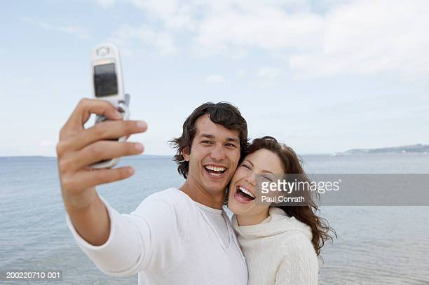 Young couple taking self-portrait with mobile phone, smiling