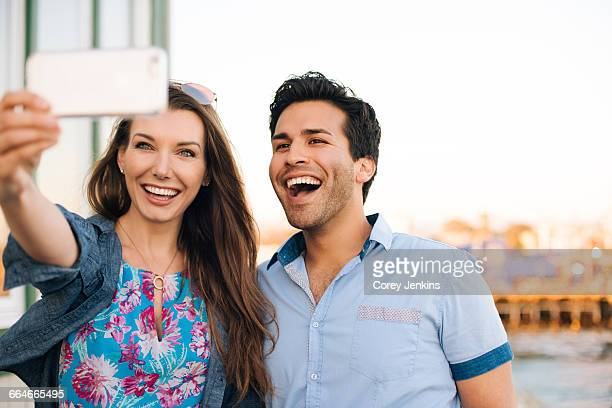 Young couple taking smartphone selfie on pier, Santa Monica, California, USA