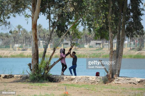 A young couple talk on the banks of the Tigris River as Iraqi families visit the vast Baghdad Island amusement park on the northern outskirts of the...