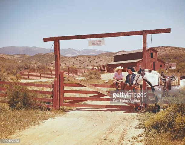 Young couple talking at ranch gate