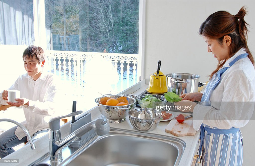 A young couple talking in a kitchen : Stock Photo