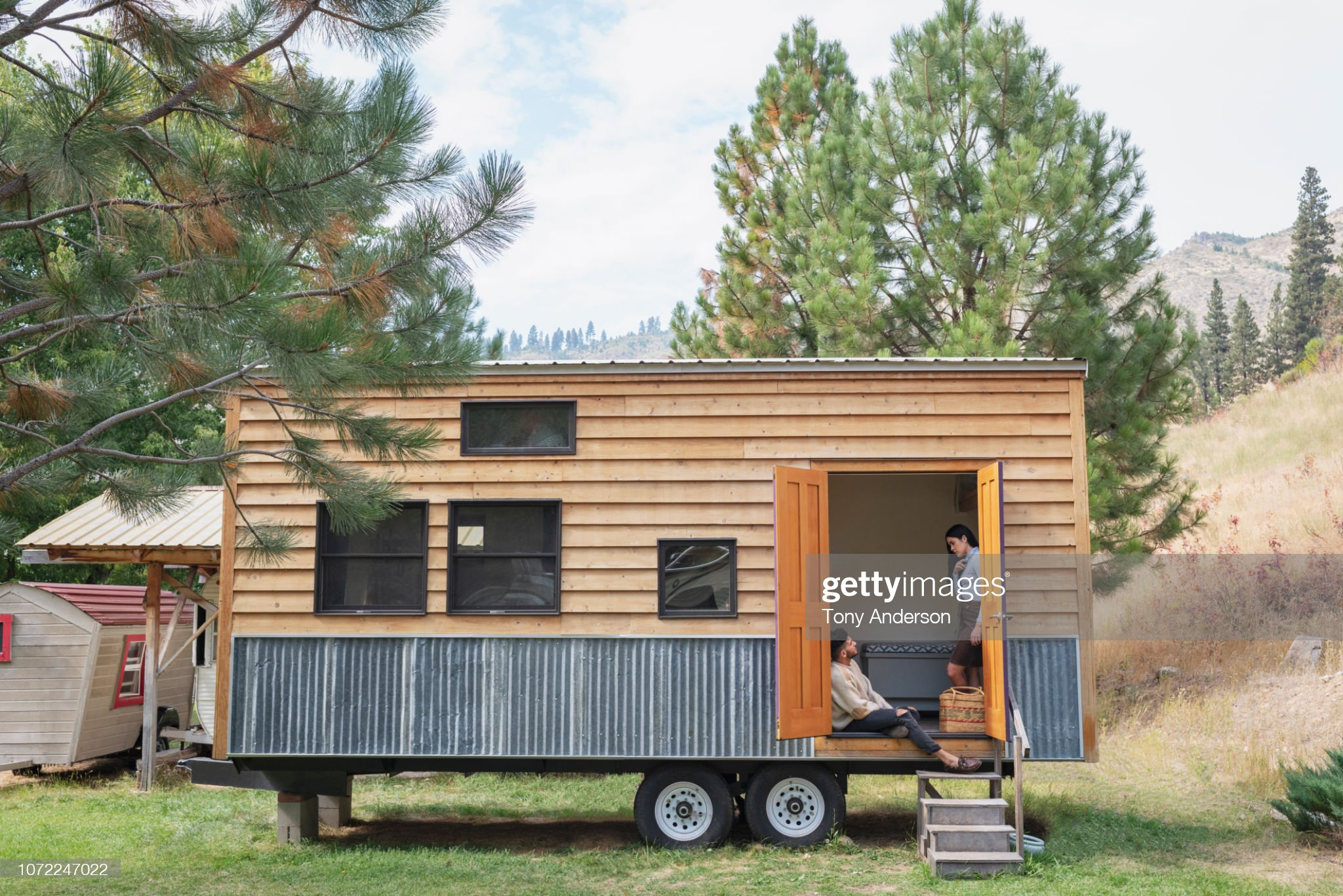 Young couple talking in doorway of their tiny house : Stock Photo