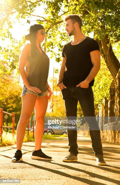Young couple talking in the sunset in a urban environment
