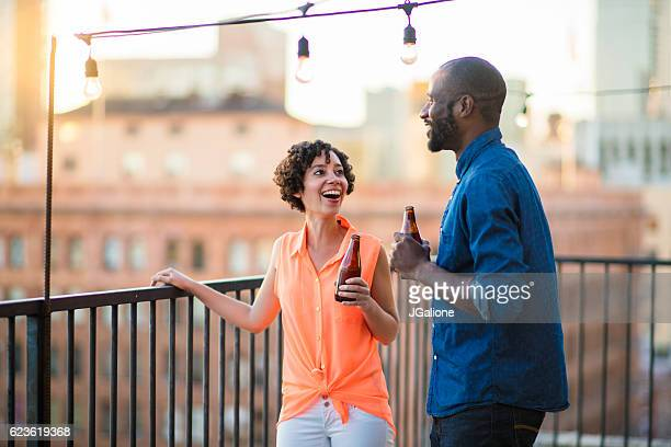 Young couple talking on a balcony in the early evening