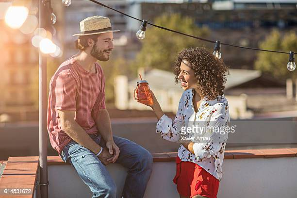 Young couple talking on a rooftop party