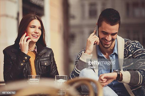 young couple talking on cell phones - coffee drink stock pictures, royalty-free photos & images