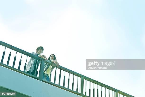 Young couple talking on footbridge