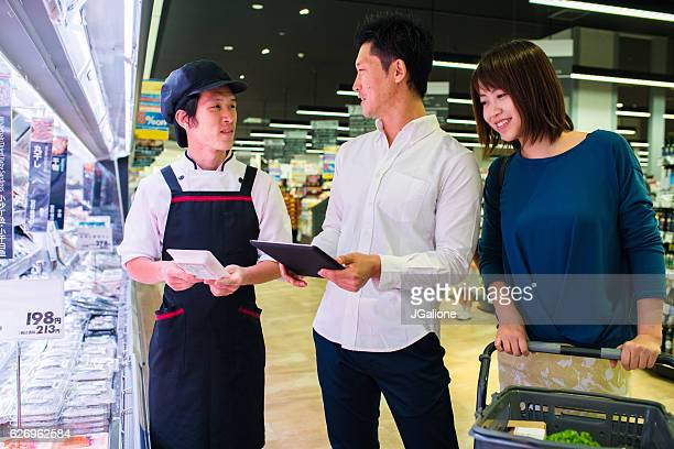 Young couple talking to a sales assistant in a supermarket